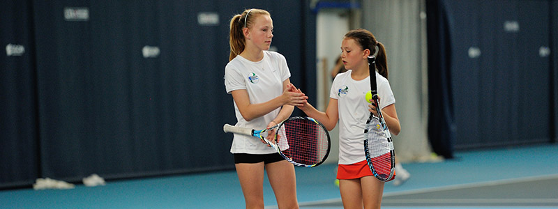 Two girls high five on a tennis court