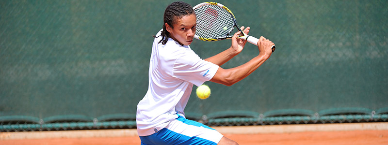A boy slides into a backhand slice on a clay tennis court