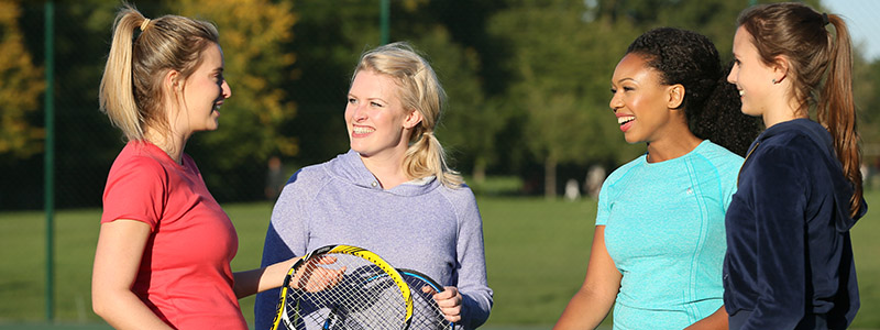 Friends playing tennis outside
