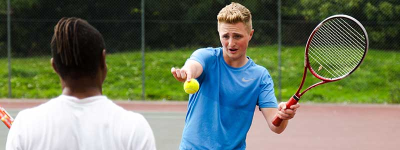 A tennis coach giving a tennis lesson on types of tennis strokes