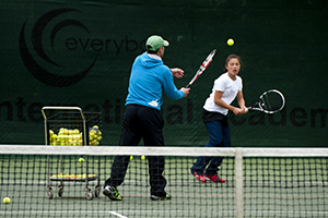 Tennis coach and player on court