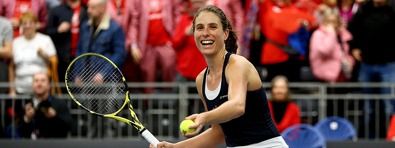 Joanne Konta hits a tennis ball into the Great Britain fans after victory in Bath